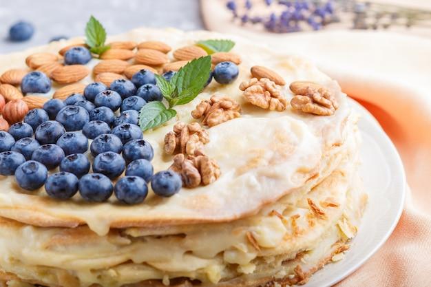 Tarta de napoleón en capas caseras con crema de leche decorado con almendras de arándanos nueces avellanas menta sobre un fondo de hormigón gris Foto Premium