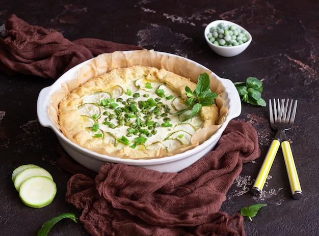 Tarta o quiche con calabacín, guisantes, cebolla verde y ricota o crema agria. Foto Premium