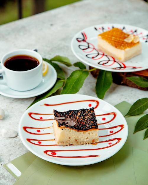 Tarta de queso adornada con jarabe de chocolate servido con té Foto gratis