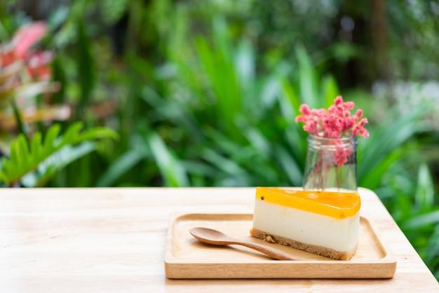 Tarta de queso de fruta de la pasión servida en madera tay y mesa de madera con florero seco Foto Premium