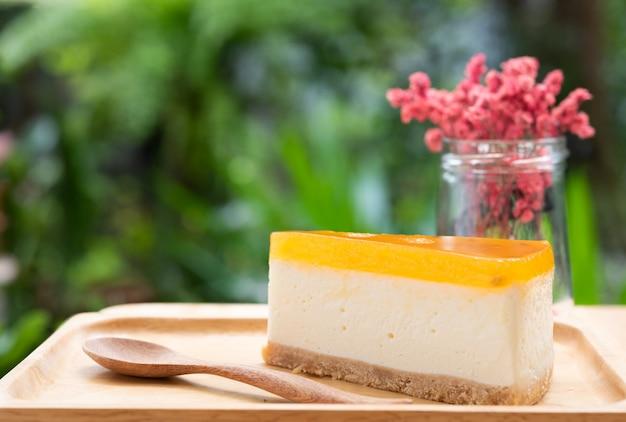 Tarta de queso de fruta de la pasión servida en madera tay y mesa de madera con flores secas Foto Premium