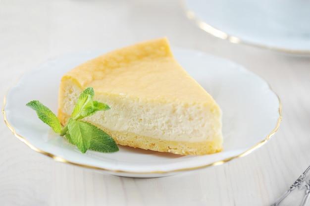 Tarta de queso y una hoja de menta en el plato con un borde dorado Foto Premium