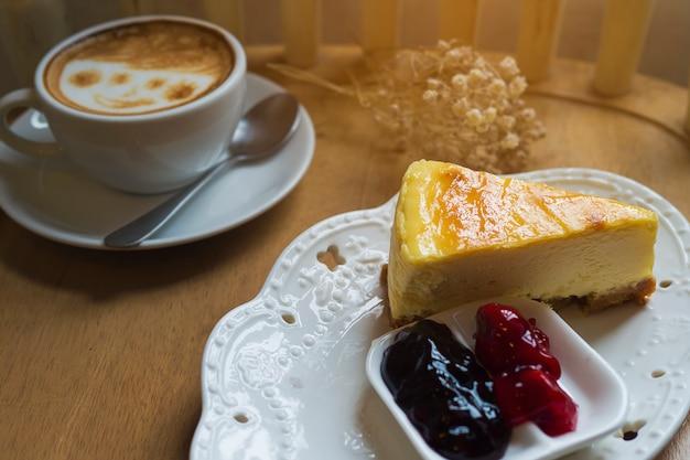 Tarta de queso con taza de café caliente en mesa de madera Foto gratis