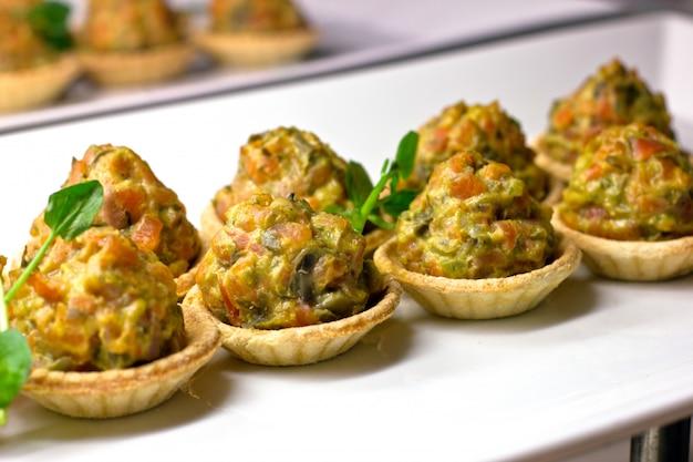 Tartaletas con verduras al horno y hierbas en una porcelana blanca di Foto Premium