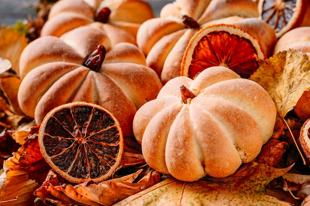 Tartas caseras en forma de calabaza con hojas de otoño de cerca. concepto de dulces de halloween Foto Premium