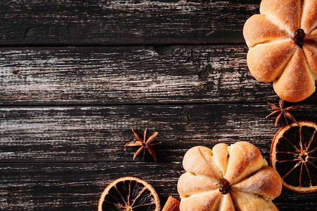 Tartas caseras en forma de calabaza y naranjas secas en madera oscura, vista superior con espacio de copia Foto Premium