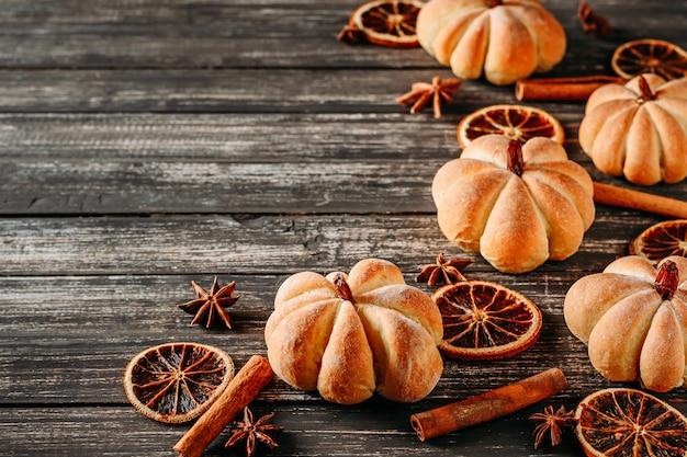 Tartas caseras en forma de calabaza y naranjas secas en una vista superior de fondo de madera oscura con espacio de copia Foto Premium