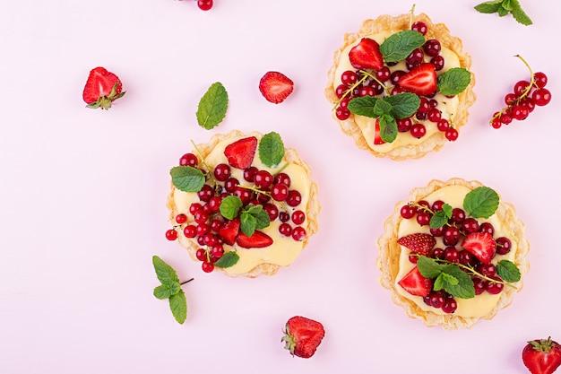 Tartas con fresas, grosellas y crema batida decoradas con hojas de menta Foto gratis