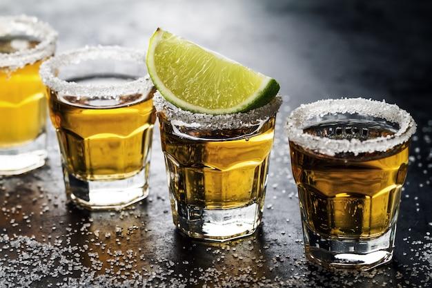 Tasty bebida de alcohol tequila cocktail con lima y sal sobre fondo oscuro vibrante. de cerca. horizontal. Foto gratis