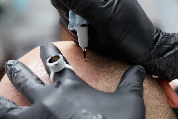 Tatuador profesional haciendo tricopigmentación de maquillaje permanente Foto Premium