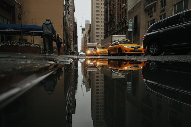 Taxis reflejados en un charco de agua Foto Premium