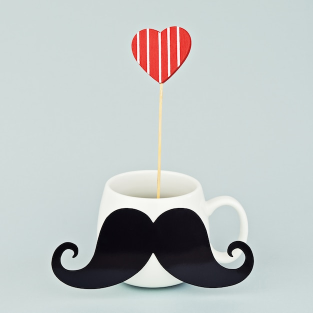 Taza blanca con bigote negro y corazón rojo. Foto Premium