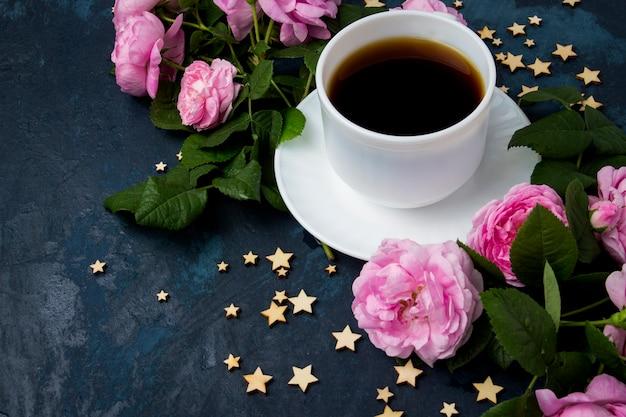 Taza blanca con café negro, estrellas y rosas rosadas sobre una superficie azul oscura Foto Premium