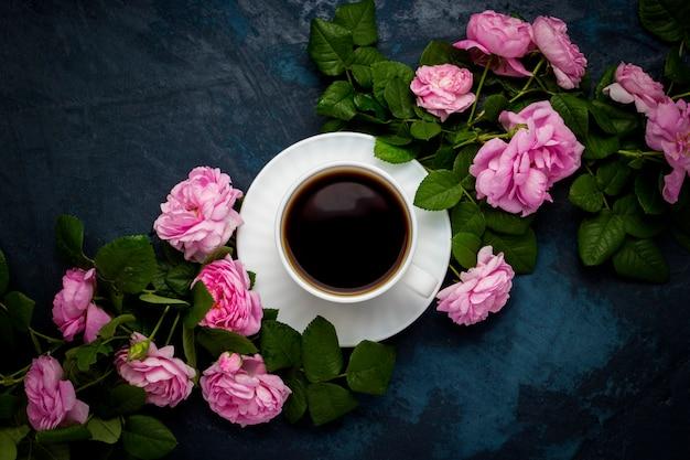 Taza blanca con café negro y rosas rosadas sobre una superficie azul oscuro Foto Premium