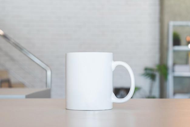 Taza blanca sobre mesa y fondo habitación moderna. Foto Premium