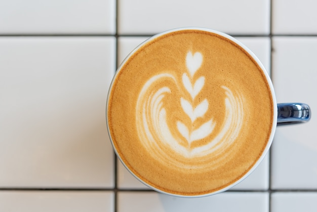 Taza de café de arte latte en mesa blanca, vista superior Foto Premium