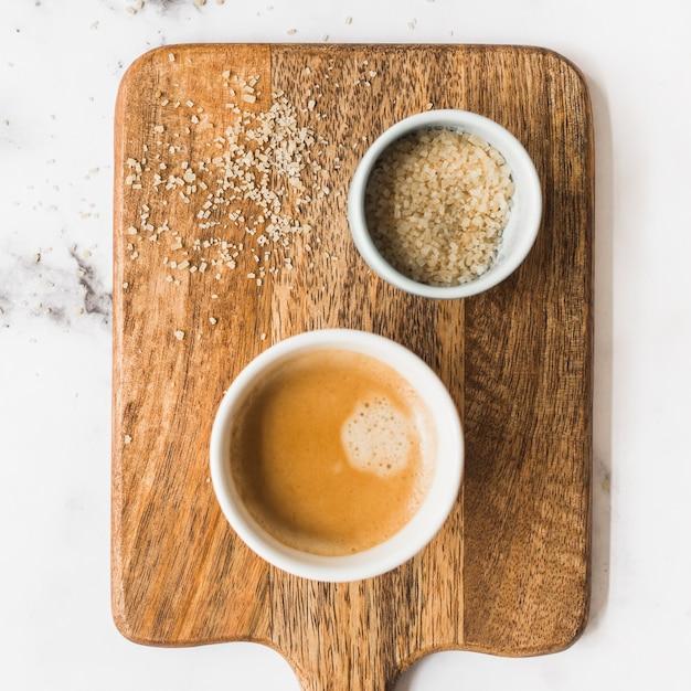 Taza de café y azúcar en la tabla de cortar de madera Foto gratis