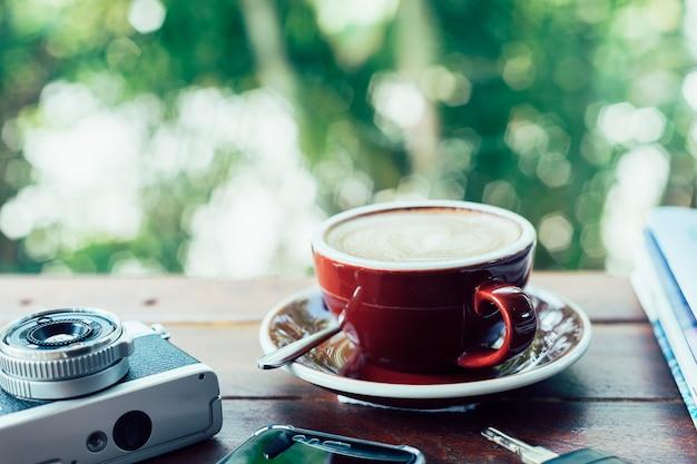 Taza de café caliente, cámara de película, libros, teléfono inteligente y llaves en la placa de madera Foto Premium