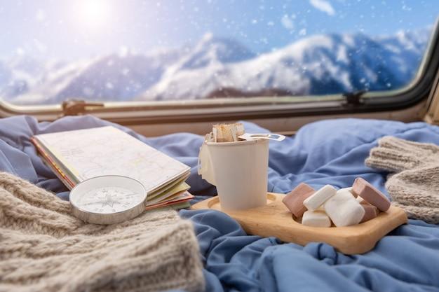 Una taza de café caliente con malvavisco cerca de la ventana con vistas a la montaña nevada Foto gratis