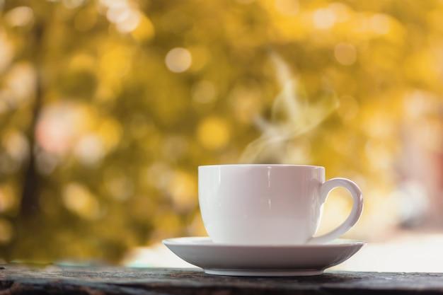 Taza de café caliente sobre la naturaleza otoño Foto Premium