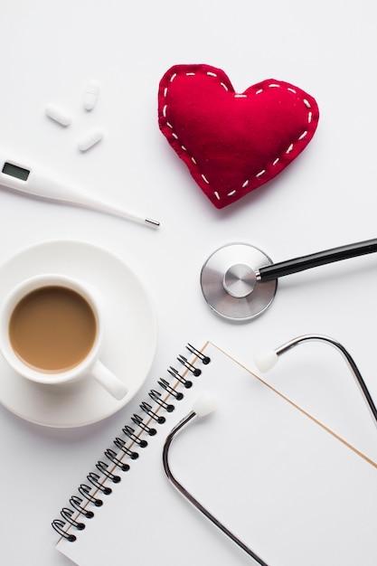 Taza de café con corazón de juguete rojo y accesorios médicos sobre escritorio Foto gratis