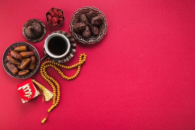 Taza de café con dátiles frutales y abalorios. Foto gratis
