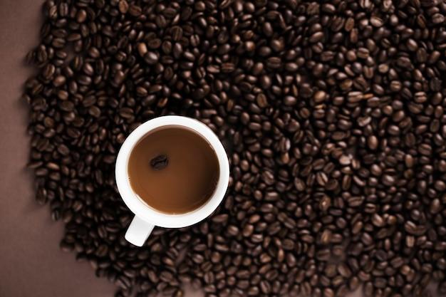 Taza de café deliciosa con el fondo de los granos de café Foto gratis