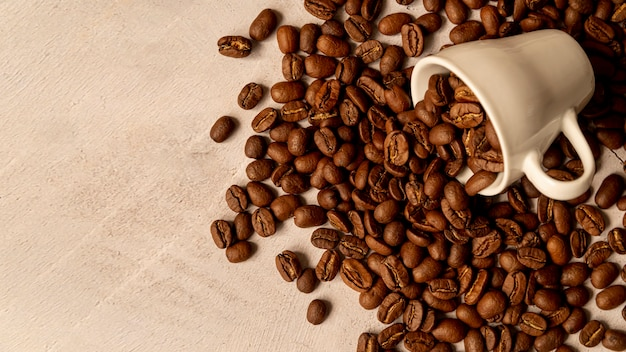 Taza de café derramada con granos tostados Foto gratis