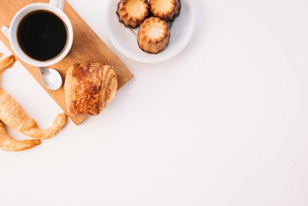 Taza de café con diferente panadería en mesa blanca Foto gratis