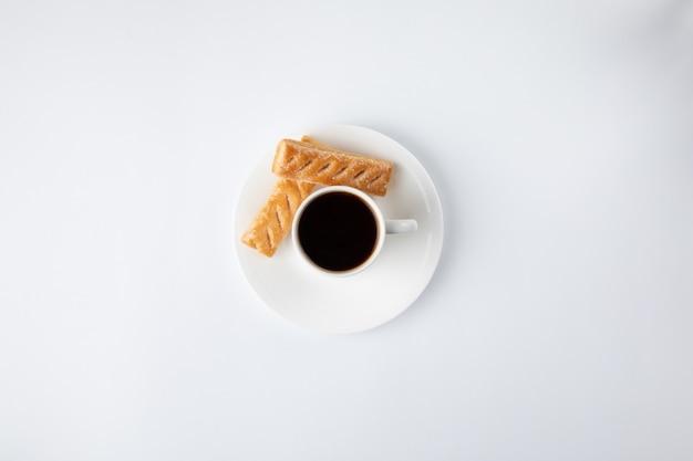 Taza de café con dulces aislados en blanco Foto gratis