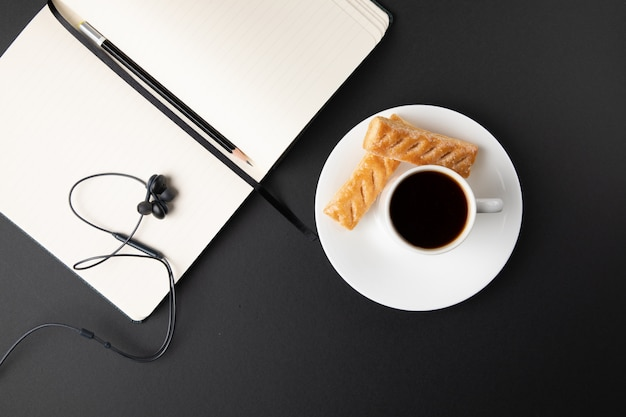Taza de café con dulces y laptop Foto gratis