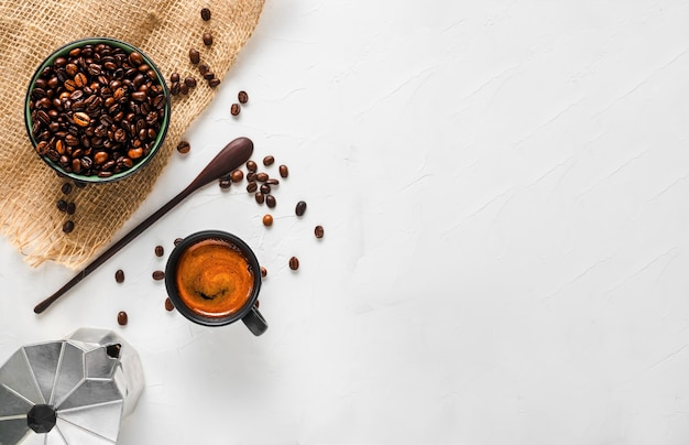 Taza de café con espresso fuerte con espuma, una cafetera y granos de café en un bol Foto gratis