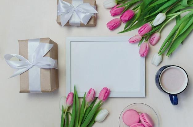 Taza de café, flores de tulipán de primavera y macarons rosados en el fondo de la vista superior de la mesa en colores pastel Foto Premium