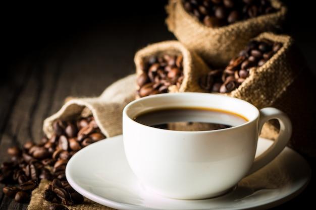 Taza de café y frijoles. café expreso y un pedazo de pastel con un rizo. taza de café y granos de café sobre la mesa. Foto Premium