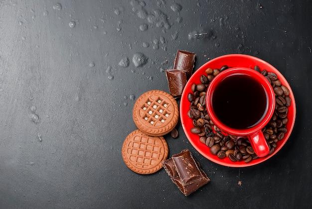 Taza de café con galletas y chocolate sobre un fondo negro Foto Premium