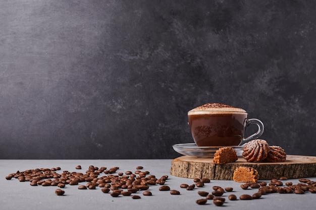 Una taza de café con granos de arábica alrededor. Foto gratis