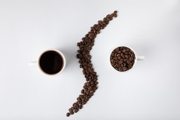 Taza de café con granos de café aislados en blanco Foto gratis