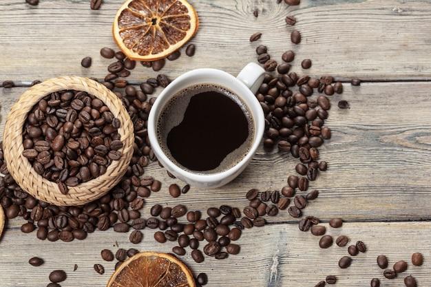 Taza de café y granos de café en madera. Foto Premium