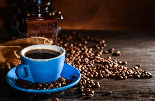 Taza de café con granos de café y molinillo de fondo Foto gratis