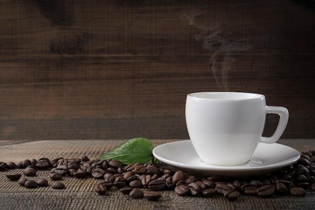 Una taza de café y granos de café sobre la mesa. fondo negro Foto Premium