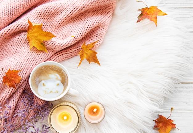 Taza de café y hojas de otoño sobre un fondo de piel Foto Premium