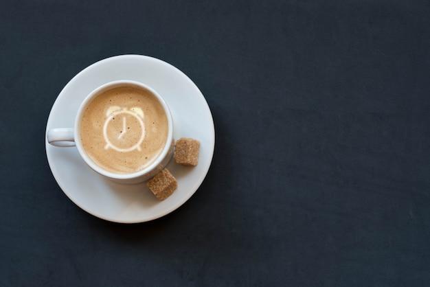 Taza de café con leche, azúcar de caña y reloj despertador firmar sobre fondo oscuro. vista superior. copia espacio Foto Premium