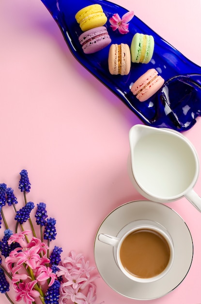 Taza de café con leche, macarrones y tarro de leche en rosa pastel Foto Premium