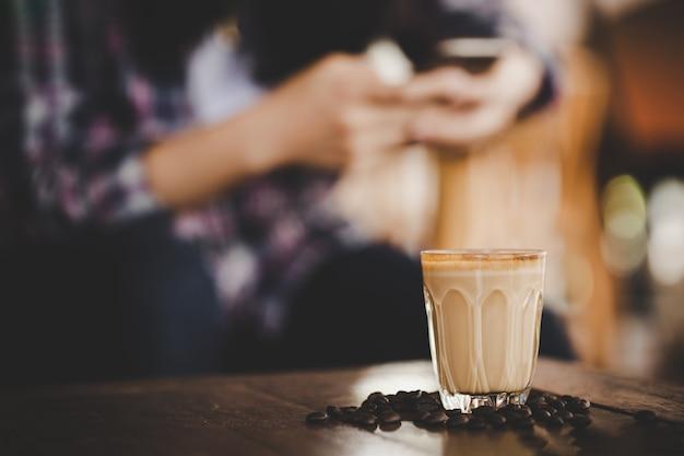 Taza de café con leche en la mesa de madera en cafetería cafetería Foto gratis