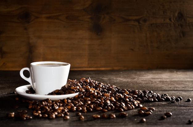 Taza de café con un montón de granos de café Foto gratis