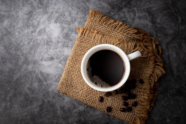 Taza de café negro y granos de café sobre cemento Foto Premium