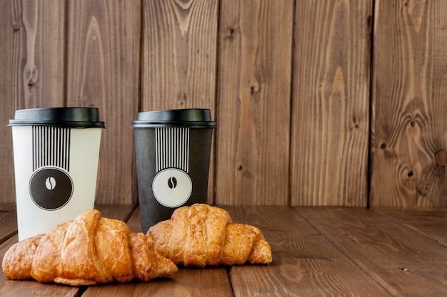 Taza de café de papel y croissants sobre fondo de madera Foto Premium