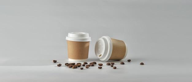 Taza de café de papel y granos de café en el fondo blanco. Foto Premium