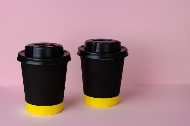 Taza de café de papel negro con una tapa sobre fondo rosa pastel. Foto Premium