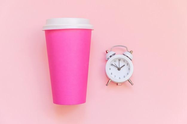 Taza de café de papel rosa de diseño laico simplemente plano y reloj despertador aislado sobre fondo colorido pastel rosa Foto Premium